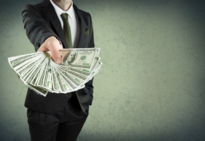 Man in suit standing holding out hand with $100 dollar bills