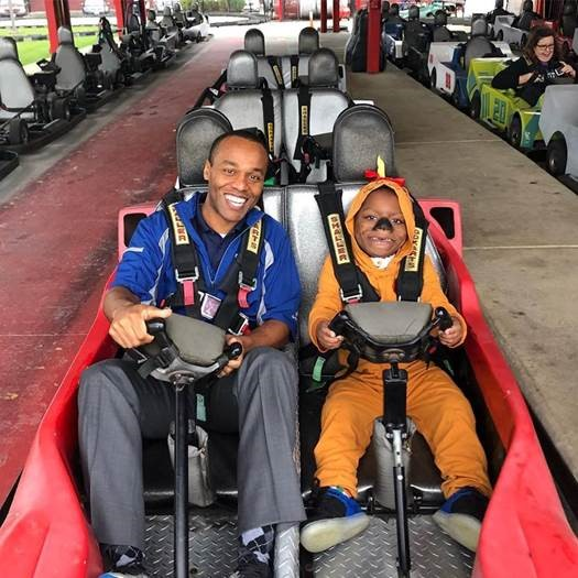 Garrison poses in a go-kart with a child at an event for A Kid Again. The nonprofit's events provide recreational experiences for children with long-term illnesses and their families.