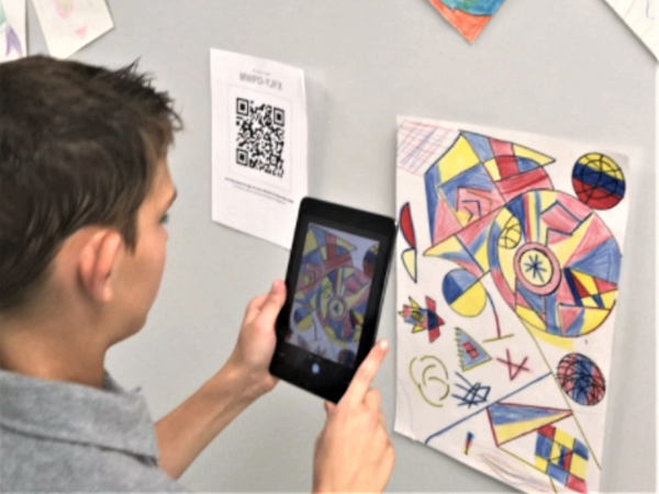 A student photographs his artwork to post on Artsonia.