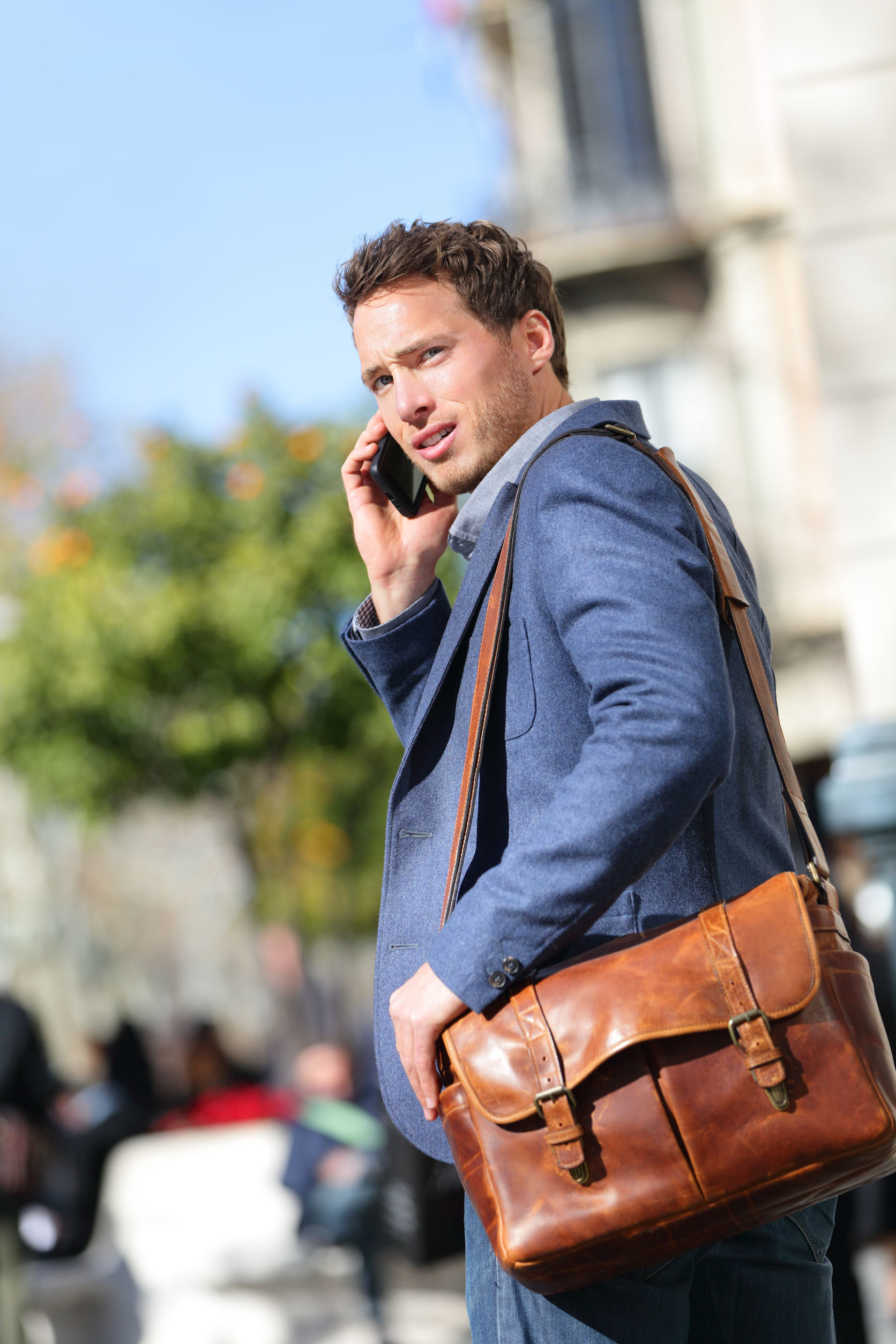 Business man on smartphone wearing jacket and leather bag