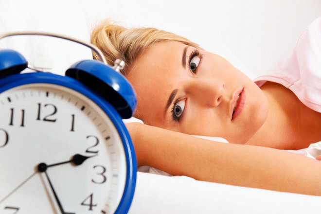 A woman lays in bed, unable to fall asleep, looking at a clock.