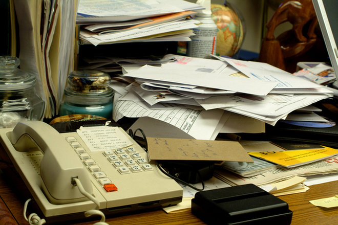 Messy desk piled with papers