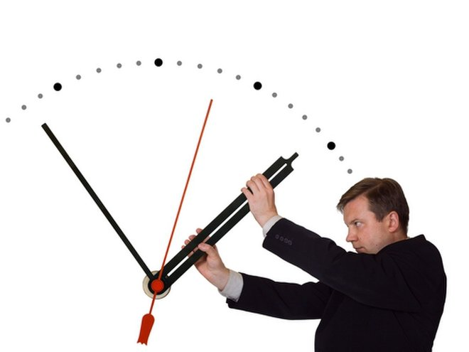 Man wrestling with clock hands